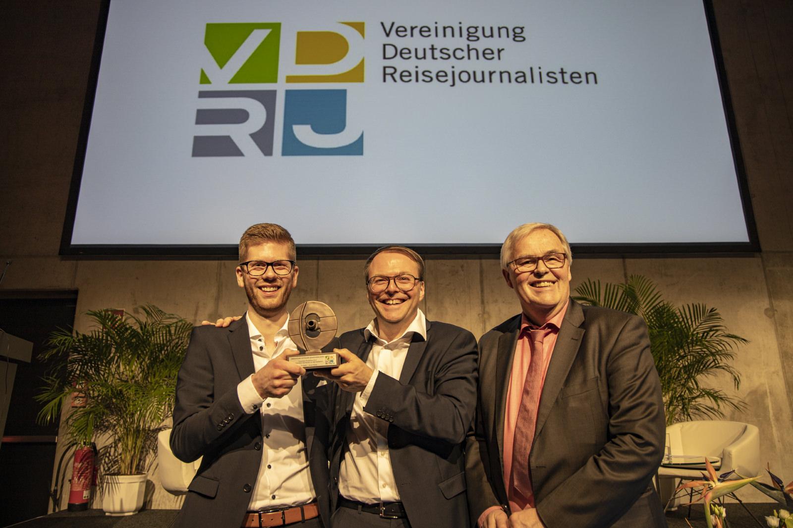 Falk Olias (l.; Geschäftsführer Runa Reisen) freut sich mit Karl B. Bock (m.; Geschäftsführer Runa Reisen) über den Columbus Ehrenpreis 2019, den ihm Rüdiger Edelmann (1. Vorsitzender & Sprecher der VDRJ) überreicht hat; Foto: Holger Leue